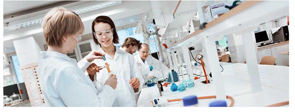 opiskelijoita laboratoriovaatteissa